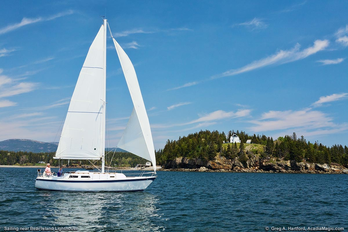 A sailboat passes by the Bear Island Lighthouse in Acadia as it leaves Somes Sound to enter the open ocean.