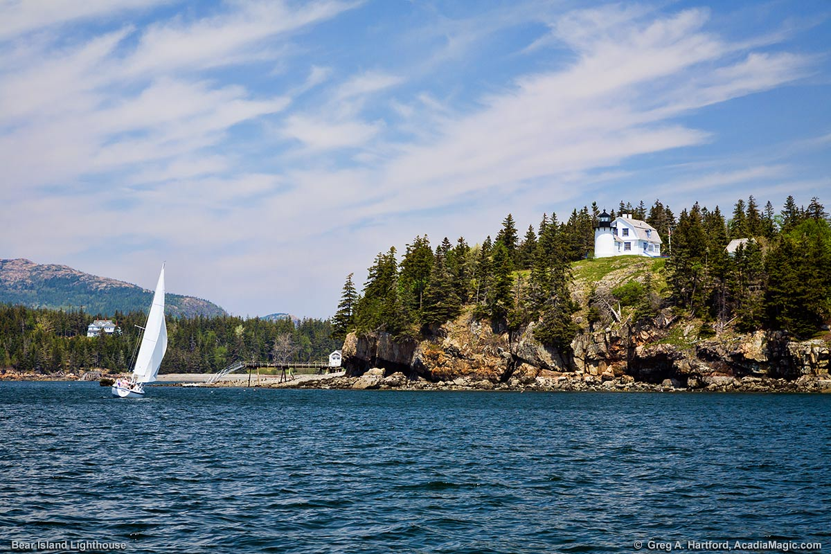 Mount Desert Island can be seen here behind the sailboat as it passes near the Bear Island Light Station.