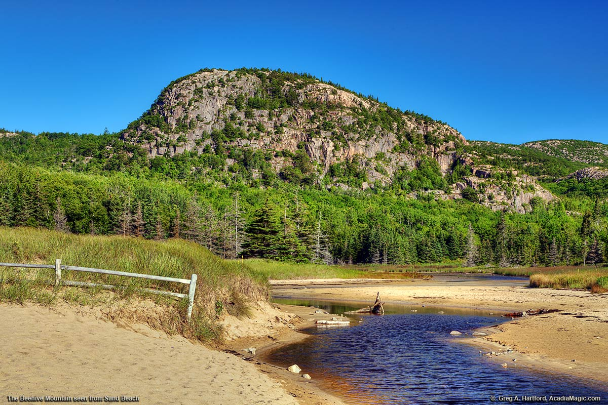 The Beehive with a sand dune fence at Sand Beach in Acadia National Park