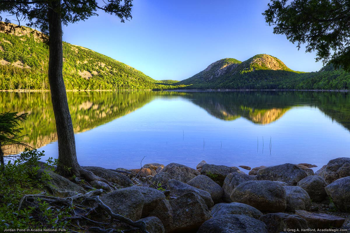 A calm Jordan Pond with reflection of The Bubbles