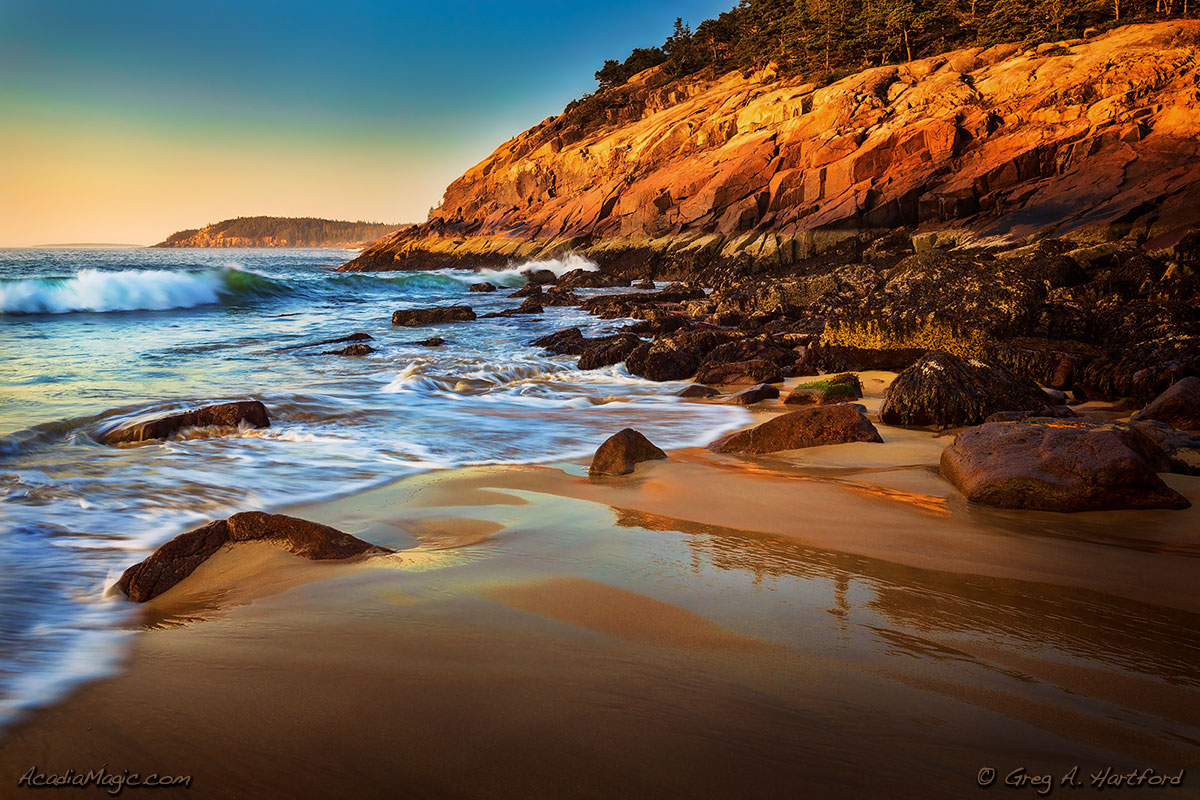 Golden morning sunlight shines on the pink granite at Sand Beach in Acadia National Park, Maine.