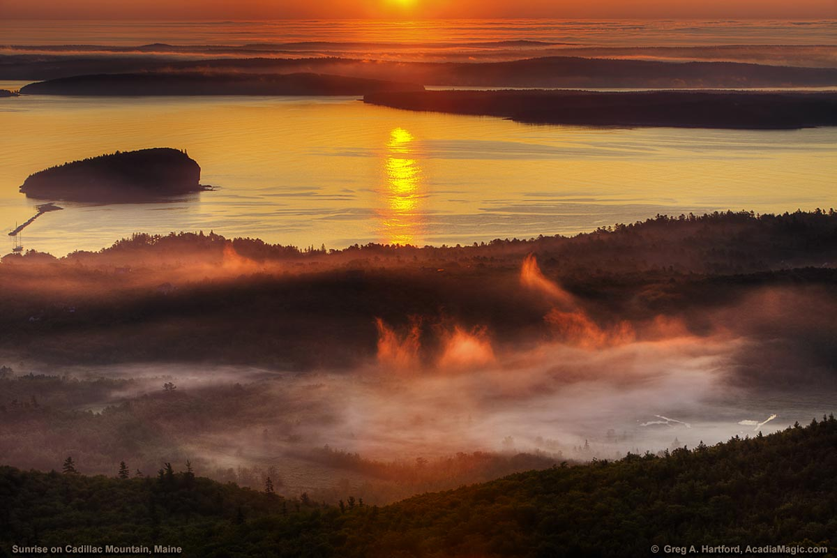 Surise lights up Bar Harbor fog seen from Cadillac Mountain in Acadia National Park