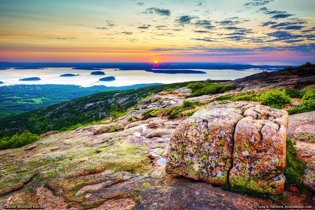 The sun rises just over the horizon as seen from Cadillac Mountain, Maine.