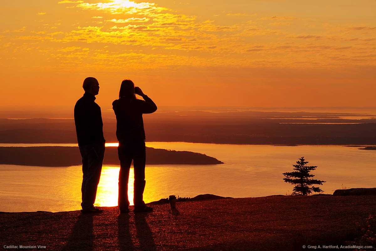A couple pauses on the Cadillac Mountain summit path to view distant islands.