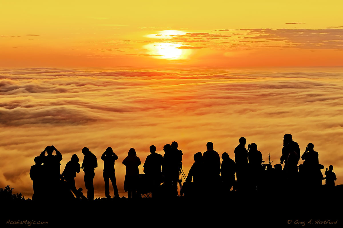 This image appears almost tribal as a large crowd stands in awe of the sunrise on Cadillac Mountain.