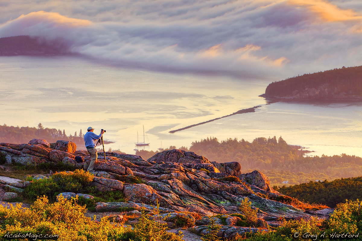 A man tries to photograph Bar Harbor, Maine at sunrise from Cadillac Mountain.