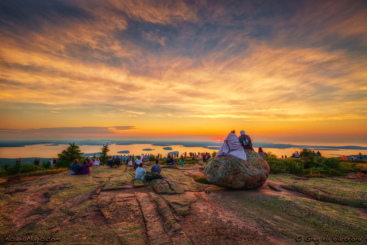 A large group of visitors gather in silence to greet another Cadillac Mountain Sunrise.