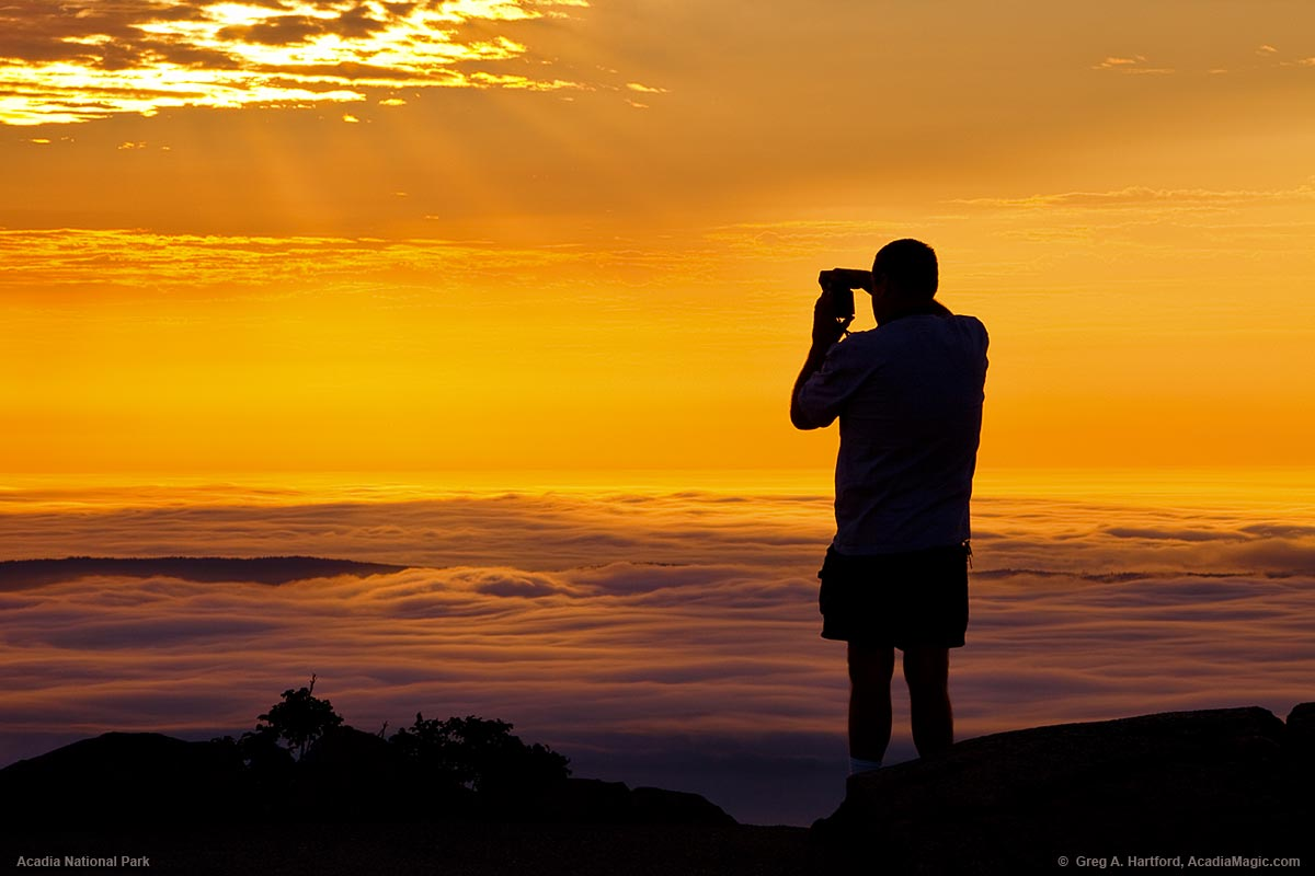 A park visitor photographs the sunrise from Cadillac Mountain in Acadia National Park.