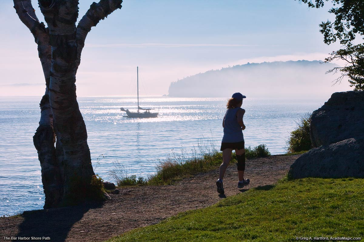 A woman is jogging on the Bar Harbor Shore Path.