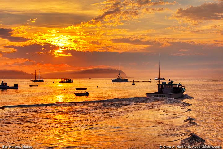 A lobster boat leaves the public pier in Bar Harbor at sunrise.