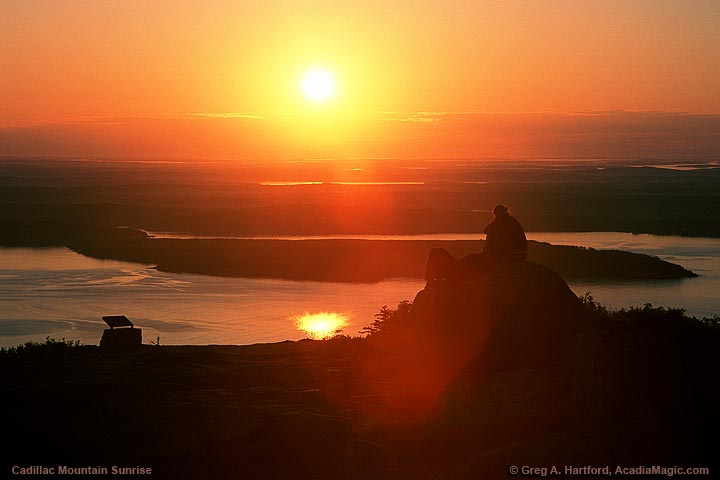 A couple watches the sunrise together on Cadillac Mountain