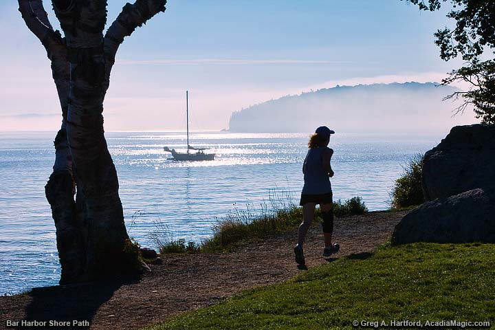 A woman jogs on the Shore Path in the morning with yacht in the distance