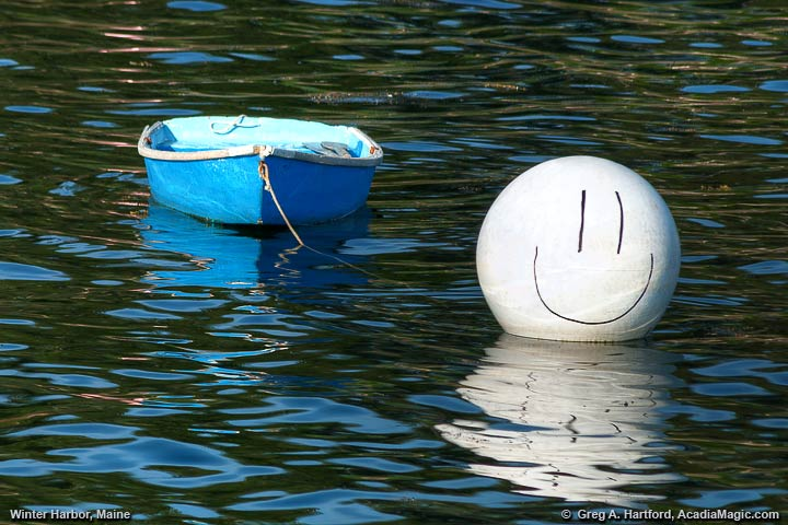Smiley face on buoy next to dinghy